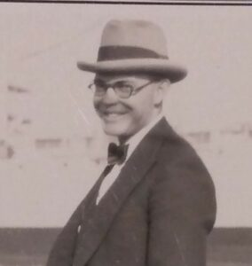 Harold Osborn in fedora and round glasses, with bow tie